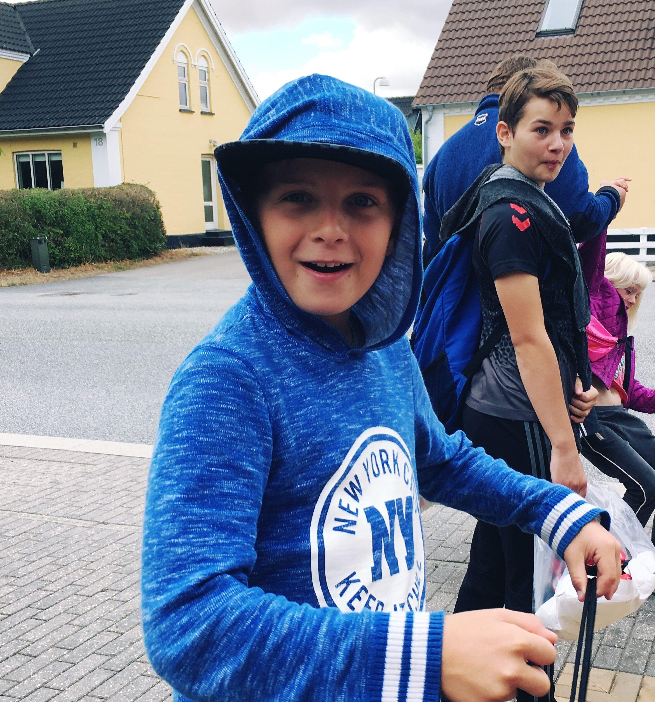 Dreng i blå hættetrøje, ved vej og hus