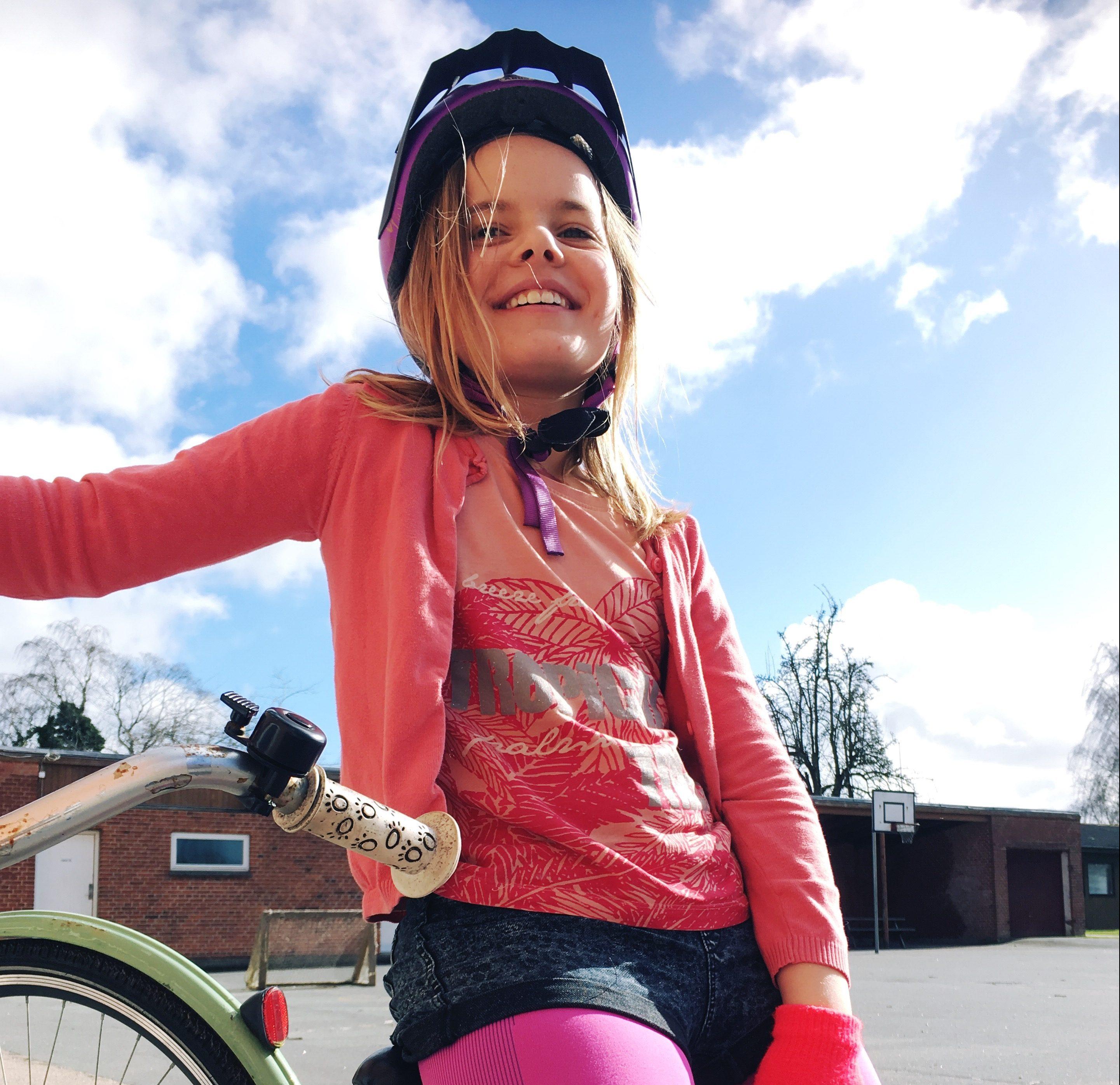 Pige med cykelhjelm og cykel, solskinsdag