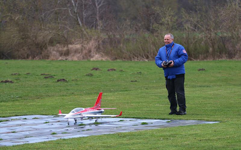 rød model flyvemaskine, mand i blå jakke på grøn græsplæne